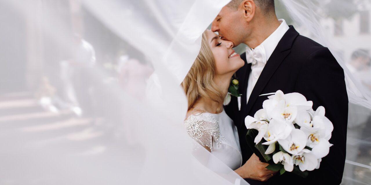 https://andradadan.com/wp-content/uploads/2020/06/groom-black-tuxedo-hugs-tender-stunning-bride-while-they-stand-1280x640.jpg